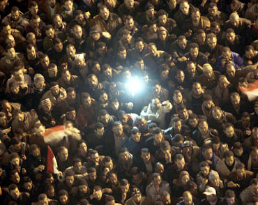 Anti-government protesters in Cairo's Tahrir Square listen as President Hosni Mubarak addresses the nation in a televised speech