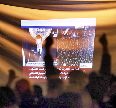 Demonstrators gesture as they listen to Egyptian President Hosni Mubarak's televised speech screened in Tahrir Square in Cairo