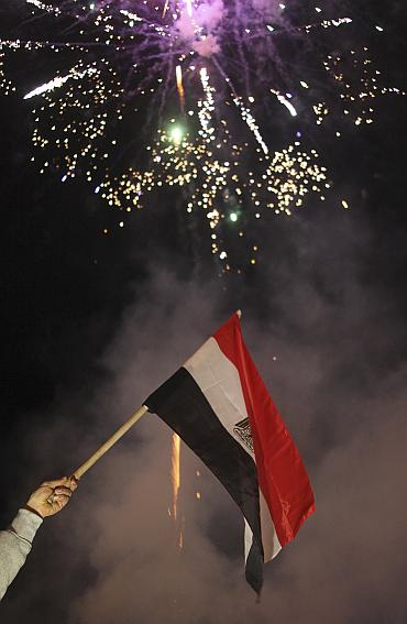 A man waves an Egyptian flag as fireworks explode during the celebration of the resignation of Egypt's President Hosni Mubarak