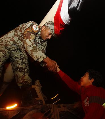 A young Egyptian shakes hands with an army officer atop a tank in Tahrir square in Cairo