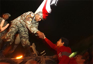 A young Egyptian is raised by his father to shake hands with an army officer atop a tank in Tahrir square in Cairo on Friday