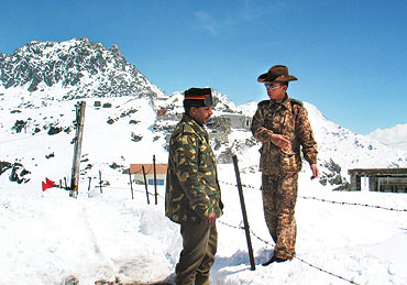 An Indian army officer talks with a Chinese soldier at Nathu-la