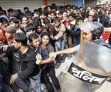 A police officer drags a man from a crowd gathered outside a bank to buy tickets for the cricket World Cup in Dhaka