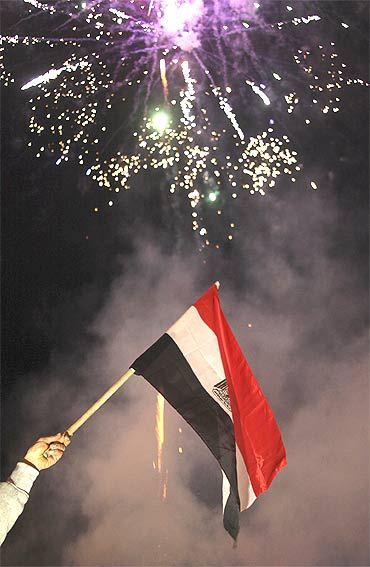 The Egyptian flag is aflutter as fireworks explode in celebration after Hosni Mubarak stepped down as Egypt president