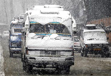 Vehicles covered with snow are driven on a road during snowfall in Srinagar