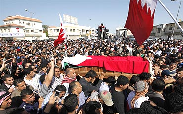 People carry the body of a protester killed during a protest on Monday, as they gather at a Shi'ite village cemetery in Sanabis