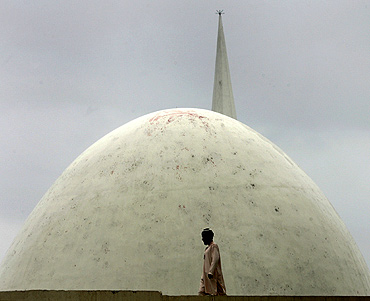 A man walks on the roof of the Red Mosque during a gathering in Islamabad to mark the first anniversary of an army raid on the complex