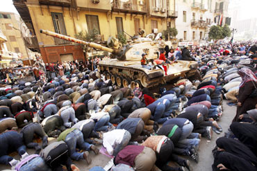Egyptian cleric Sheikh Egyptian pro-democracy supporters pray next to an army tank during Friday prayers in Tahrir Square
