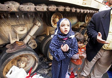 A girl attends Friday prayers in front of an army tank in Tahrir Square