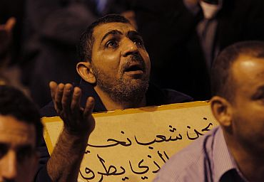 A man prays for demonstrators who were injured after riot police stormed an anti-government protest camp, outside the Salmaniya hospital in Manama