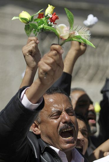 Oppn MP Ahmad Saif Hashid shouts slogans as he waves roses during an anti-government protests