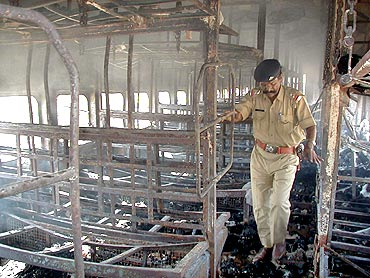 A file photo of a policeman inspecting the charred carriage of the Sabarmati Express