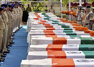 CRPF personnel pay their last respects near the coffins of policemen who died in a Maoist attack