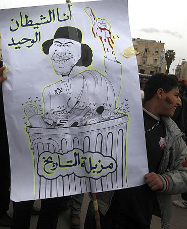 An anti-government protester holds a banner depicting Libyan leader Muammar Gaddafi in Benghazi city, Libya, on February 23. The characters read 'I am the only devil' (top) and 'the waste bin of history'