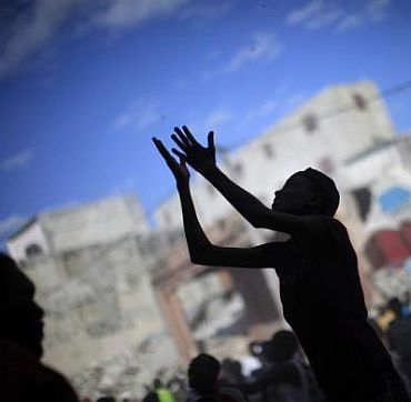 A woman raises her arms for products as people loot a destroyed shop in Port-au-Prince