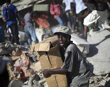 A youth loots products from a destroyed store in Port-au-Prince