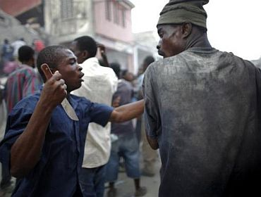 A looter holds a knife as he fights for products in Port-au-Prince