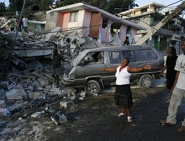 A woman reacts near destroyed buildings after the earthquake devastated Port-au-Prince