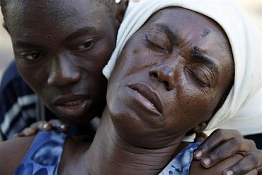 A girl comforts her injured mother at a makeshift hospital in Port-au-Prince