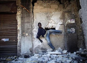 A looter leaves a damaged building through a hole in a wall in downtown Port-au-Prince