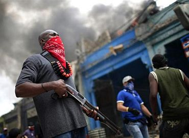 A private security guard stands outside a burning store in downtown Port-au-Prince