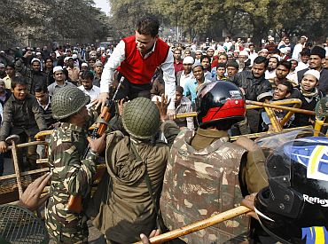 Demonstrators scuffle with security personnel during a demonstration in protest against efforts by local authorities to demolish what police described as an illegally built mosque in New Delhi
