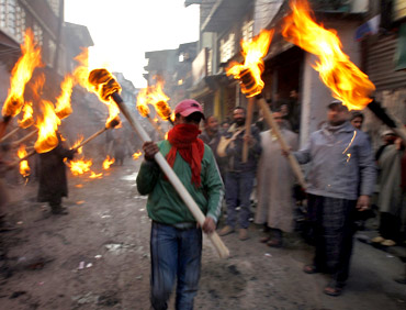 Activists of the Jammu Kashmir Liberation Front hold torches during a procession to mark International Human Rights Day in Srinagar