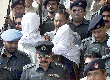 Pakistani police escort Sheikh Omar (L) and Sheikh Adil inside the premises of a judicial court in Karachi