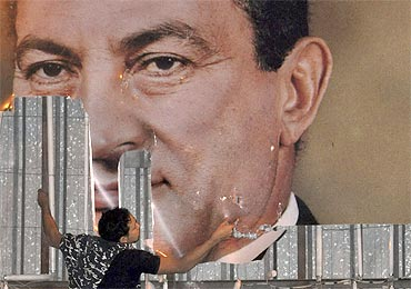 An anti-government protester defaces a picture of Egypt's President Hosni Mubarak in Alexandria