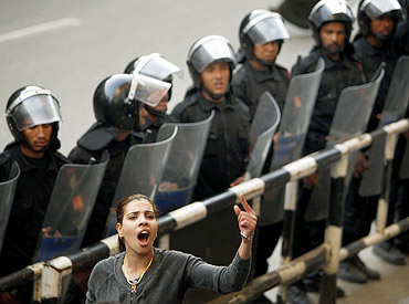 A member of an Egyptian activist group, shouts anti-government slogans in front of a police cordon during a demonstration in Cairo
