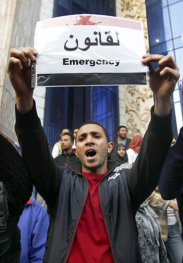 A protester displays a message on a placard of the Egyptian flag during a demonstration