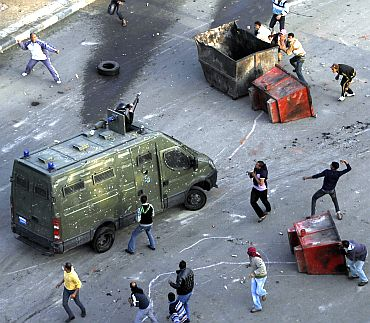 Egyptian anti-government protesters attack a riot police car at the port city in Suez