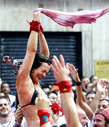 A reveller gets sprayed with wine during the start of the San Fermin Festival
