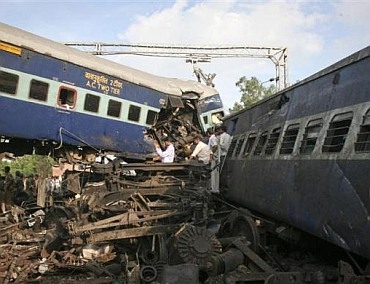 People search the mangled carriages of a derailed Kalka Mail.