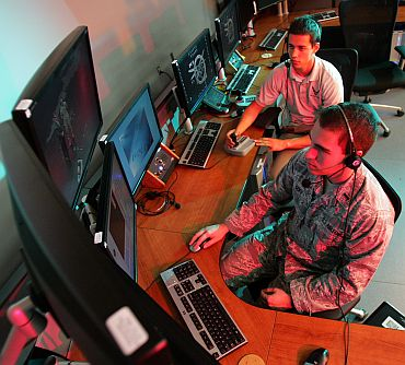 US Air Force First Lieutenant Zachary Goff (foreground), and Chris Allen, a student from Ohio State University, operate the control console to run a test flight of a drone