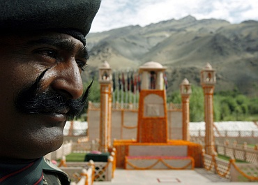 An Indian army soldier stands near the war memorial during a wreath laying ceremony during Vijay Diwas in Drass