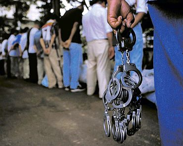 A guard with handcuffs watches prisoners arrive at the Carandiru Penitentiary prison in Sao Paulo