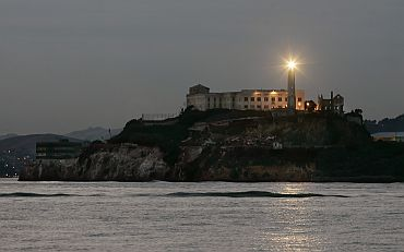 Lighthouse on the former island prison of Alcatraz flashes at dusk in San Francisco Bay
