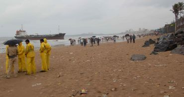 People gather at the beach to watch the stranded ship