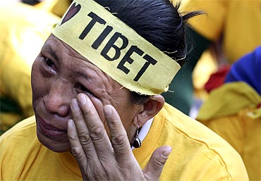A Tibetan exile wipes her tears during a protest against China