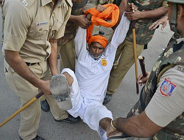 A supporter of yoga guru Ramdev is detained by police at Ramlila grounds in New Delhi