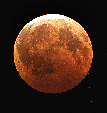 The moon is engulfed in the earth's shadow during the peak of a rare total lunar eclipse as viewed through a telescope