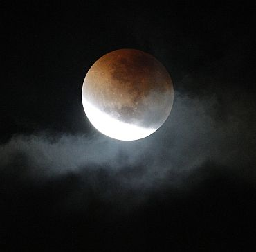 A lunar eclipse is visible through a gap in storm clouds over Sydney in the early hours of June 16