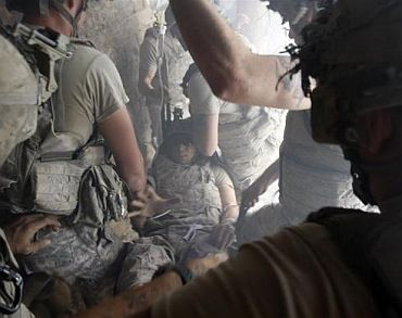 A US soldier, wounded by sniper fire, is evacuated by his comrades in the village of Bargematal, Nuristan province