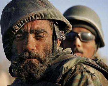 A dust-covered Afghan National Army soldier with a flower tucked behind his ear rides on the back of a vehicle during a patrol near Panjwaii town