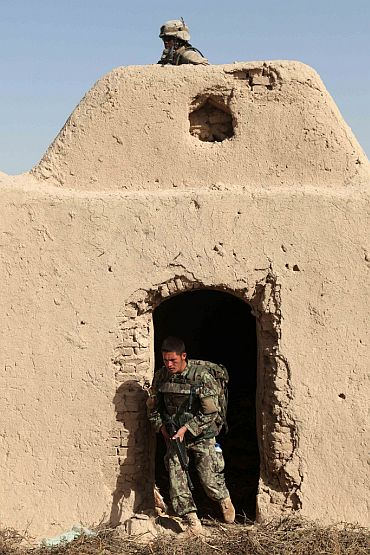 A US Marine, top, and an Afghan National Army soldier clear a building during a patrol in Sangin Valley, Helmand province, Afghanistan