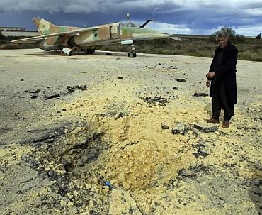 A man shows a crater caused by what he says is the impact of a missile fired from a Libyan army aircraft as he stands in front of an old military plane at a military airport runway in the eastern Libyan town of Al Abrak