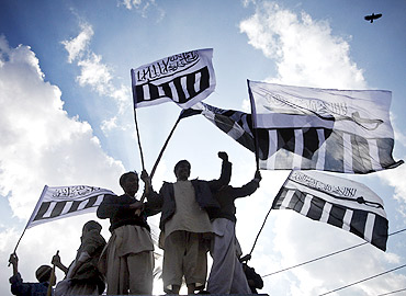 Supporters of Jamaat-ud-Dawa hold party flags during a rally against Davis in Lahore