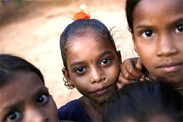 Girls react to the camera outside their hut in a small hamlet on the outskirts of Jeypore village in Orissa