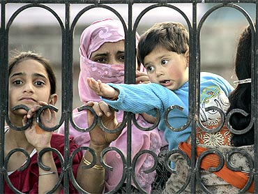 A Kashmiri woman, with her children, looks through a gate, outside Baadam Vaer, during its re-opening ceremony in Srinagar